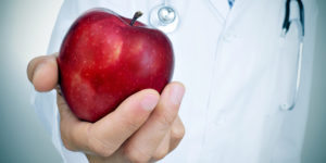 Closeup of a young caucasian doctor with a red apple in his hand, depicting the idea of the healthy eating  as a basis for a good health